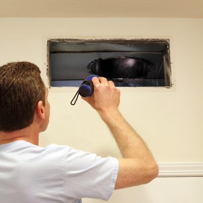 man looking at air duct